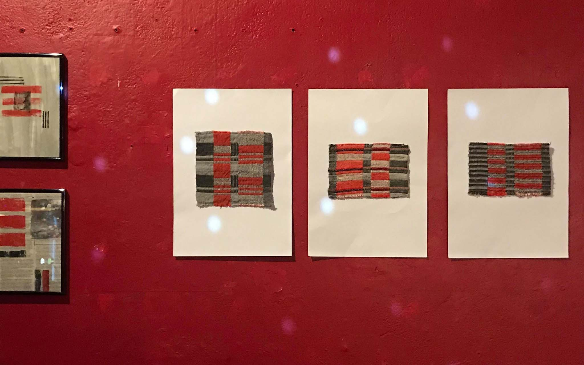 A series of three textile prints on a red wall