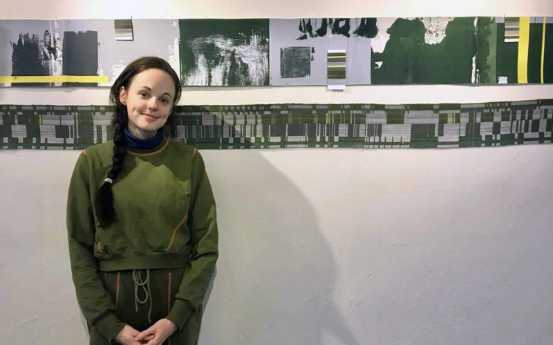 Rebecca Hiscock, BA Textile Design Graduate, standing in front of her textiles work exhibited at Norwich Playhouse