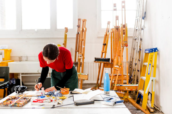 - Student working in the Norwich University of the Arts painting studios, painting with easels behind