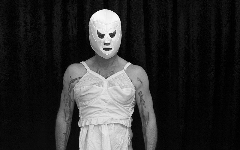 Photo with a dark background showing a man wearing a white slip dress and white face mask