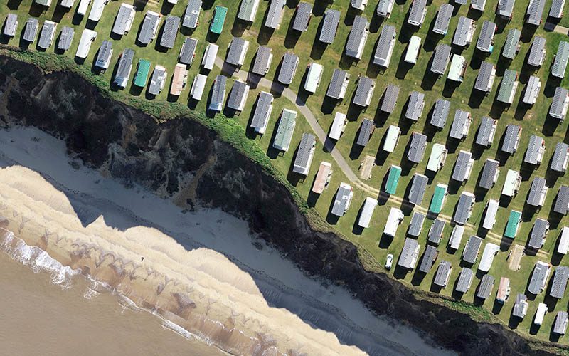 Image of a beach from above showing the line of the cliff and many rows of static caravans