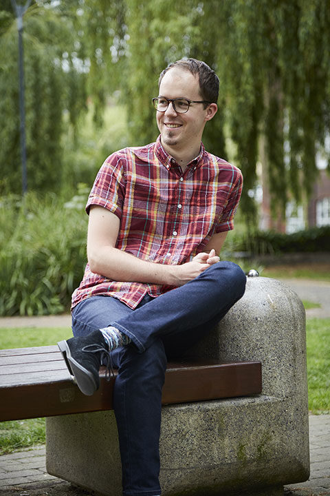 BA Illustration student William Black sits outside Norwich University of the Arts wearing a red checked shirt and jeans
