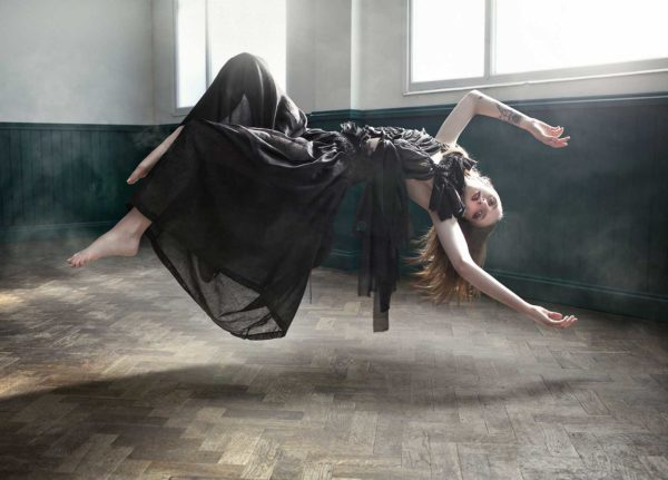 Annabel Leech, MA Fashion. Photography by Kev Foster.  - Photograph of a woman levitating, wearing a black dress and reclining backwards in the air