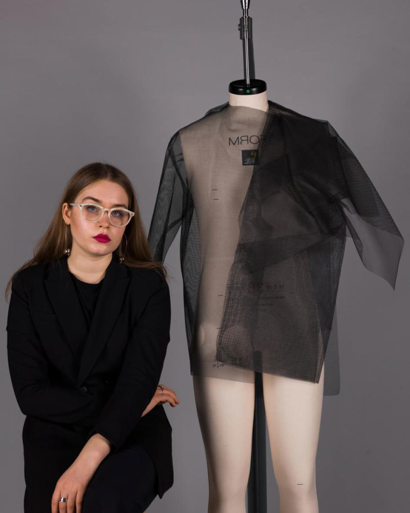 BA Fashion student Eli Kiko sat in front of a draped mannequin at Norwich University of the Arts