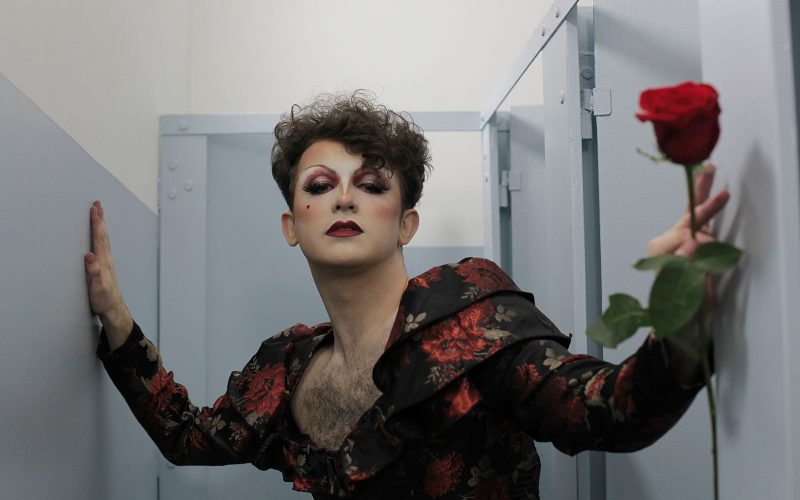 House of Drag act LIV wearing a red and black outfit and holding a red rose
