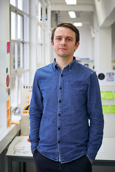 BA Illustration Lecturer Rob Nicol standing in an illustration studio at Norwich University of the Arts wearing a denim shirt