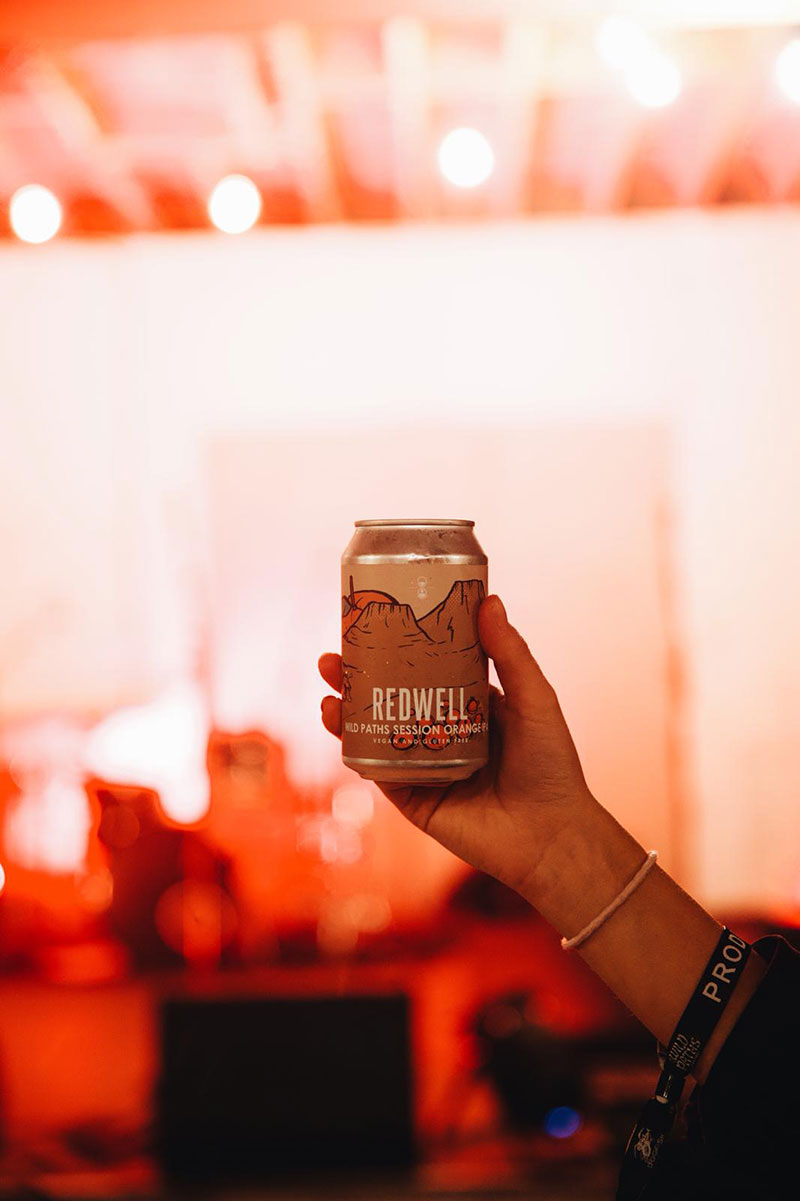 A hand holding a can of Redwell Beer in a dark venue at Wild Paths Festival, Norwich