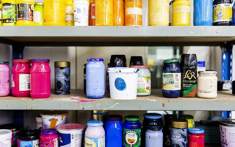 Photo of three shelves full of brightly coloured jars of paint and ink in yellows, blues and pinks