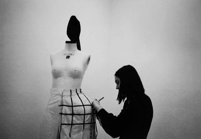 A black and white photograph of BA Fashion student Emily Saunders constructing a garment on a mannekin