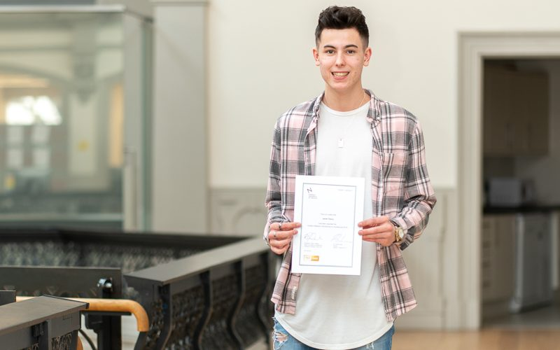 A smiling Jacob Cherry, winner of the Feilden+Mawson Scholarship for Architecture, holds his award certificate in Boardman House.