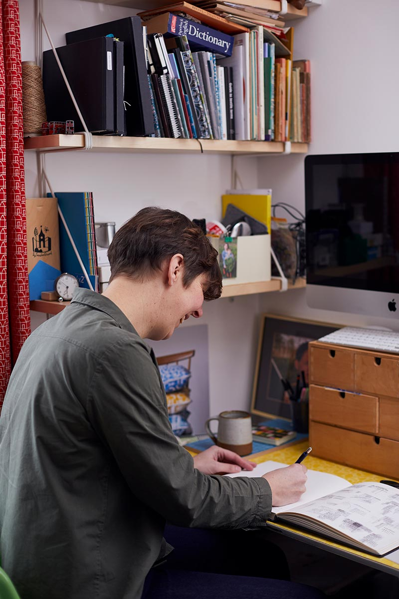 Kate Farley working in her home studio in front of shelves of books