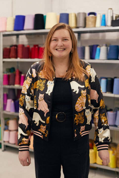 BA Textile Design Lecturer Lucy Robertson at Norwich University of the Arts standing in front of colourful yarn