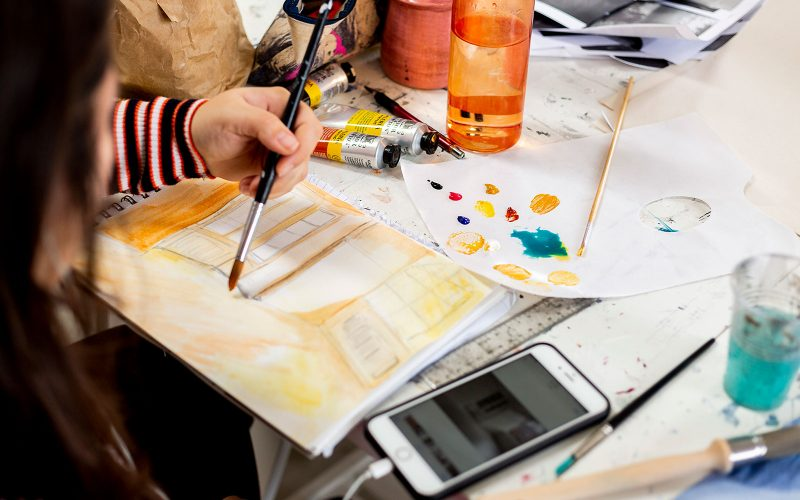A Student holding a paint brush at Norwich University of the Arts, painting on a sketch book with a phone next to her surrounded by oil paints and a water bottle
