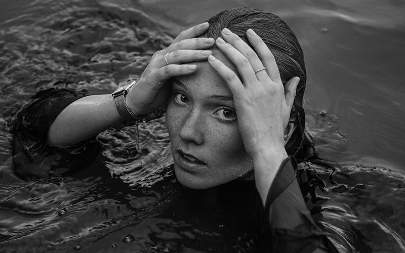 Black and white photo of a young woman in water with her hands on her forehead looking up at the camera