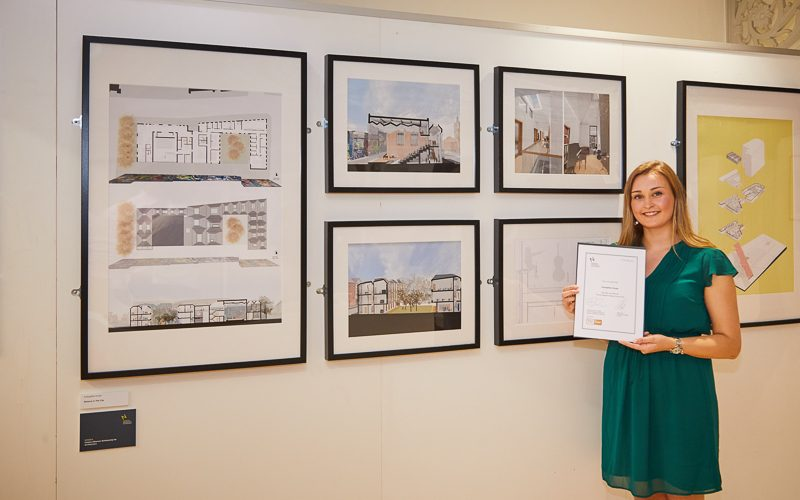 Evangeline House, winner of the Purcell Research Report Prize stands proudly in front of her winning work holding her award certificate.