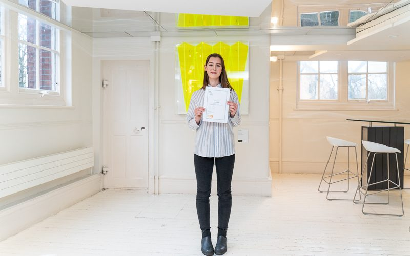 Fashion Communication and Promotion (FCP) student Emily McLeister stands smiling whilst holding her certificate for winning the Richardson Brown Travel Prize 2019
