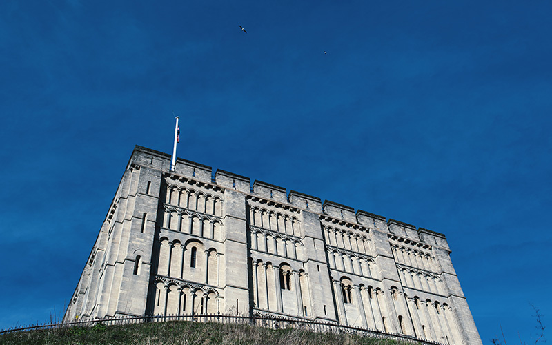 Norwich castle against a bright blue sky shot from below so it's angled up towards the sky