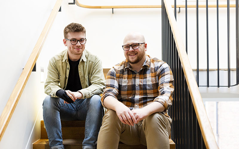 Two men sat next to each other on a staircase and smiling at the camera