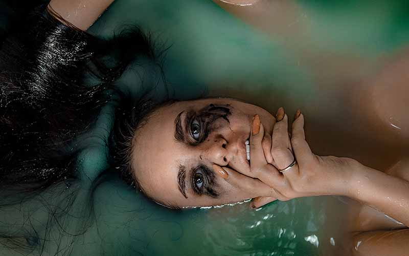 A woman with long dark hair and smeared eye makeup lying face up in a bath full of green water