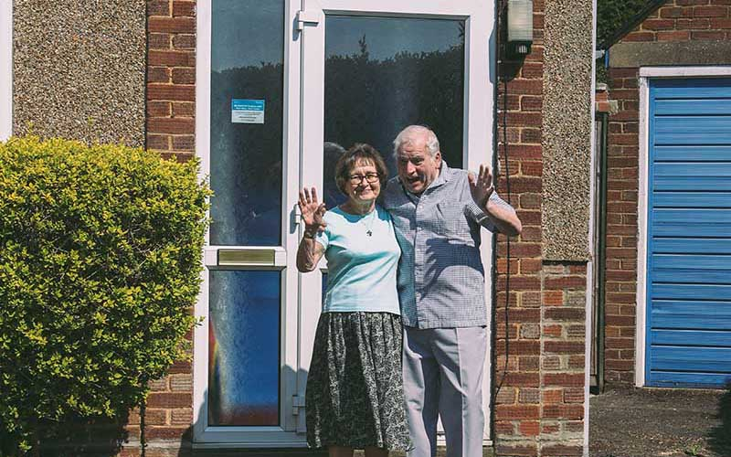 An elderly couple stood together in front of their front door, smiling and waving at the camera