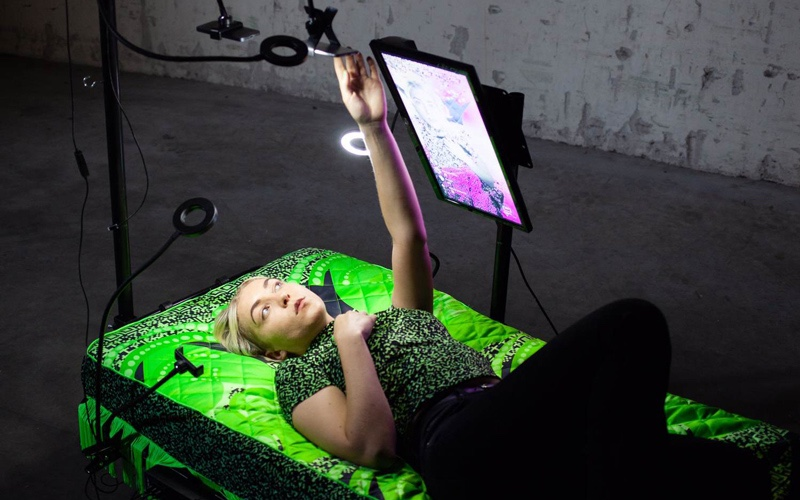 BA Illustration graduate Felicity Morris with her Masters project 'Post-Bed-Post'. She lays on a bright green mattress, which acts as a green screen, surrounded by blogger ring lights. The bed live streams to social media.
