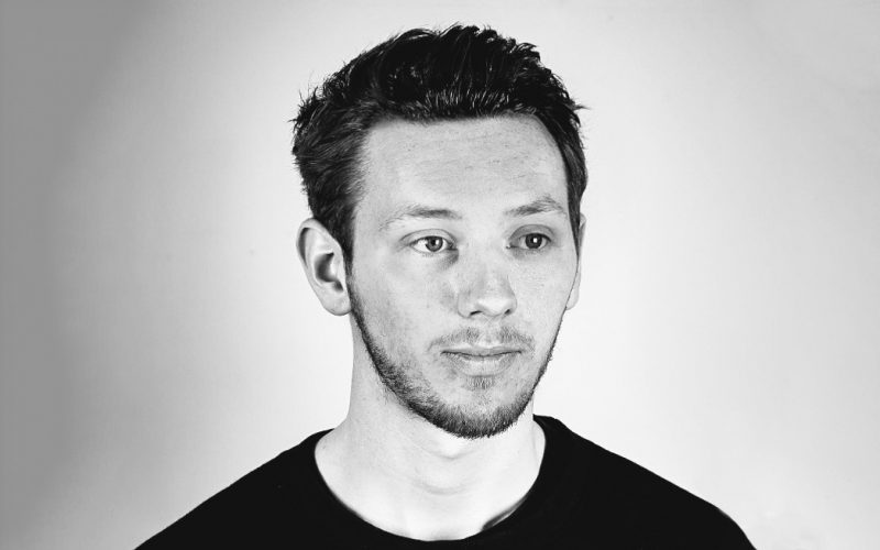 A black and white headshot of BA Graphic Communication graduate Jake Gilbert, who now works for Pentagram as a graphic designer
