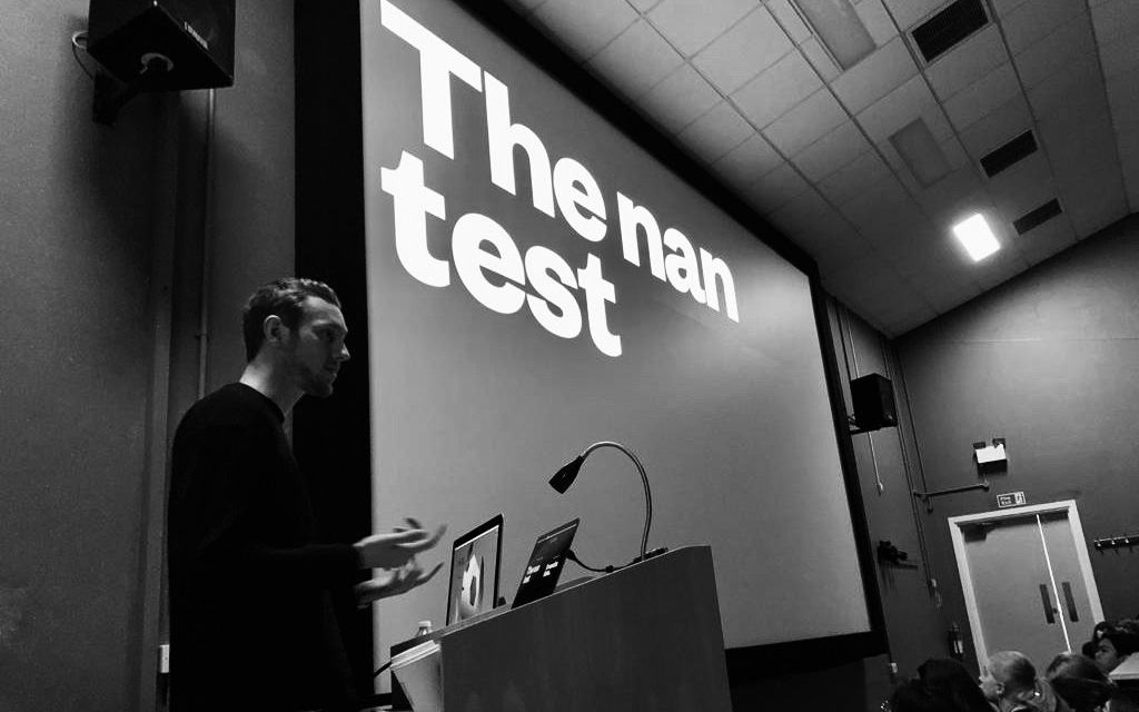 A black and white photo of BA Graphic Communication graduate Jake Gilbert in the NUA lecture theatre, presenting a slide on what he calls 'The Nan Test' to current NUA students