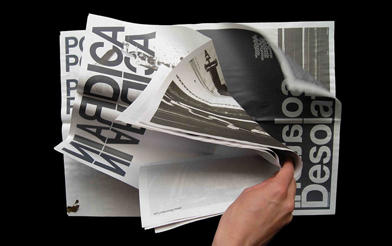 An aerial shot of BA Graphic Communication graduate Jake Gilbert holding open a typographic newspaper, showing a mixture of black and white photography and large, bold typography