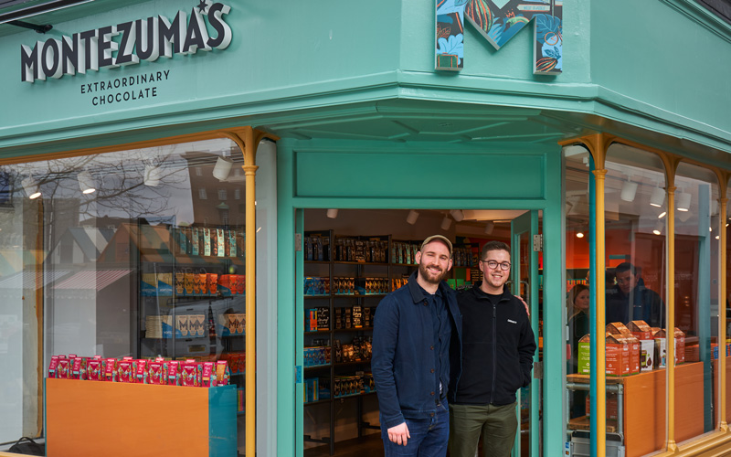 Design Director Chris Murdoch and Junior Designer Andy Coy of Butterfly Cannon design agency, and BA Graphic Design graduates, stand in the doorway to chocolate shop Montezuma's on Gentleman's Walk in Norwich. Chris and Andy both branded the chocolate company.