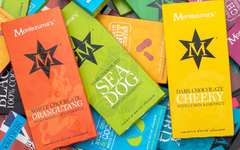 A flatlay of colourful chocolate bar packaging showing the previous Montezuma's branding