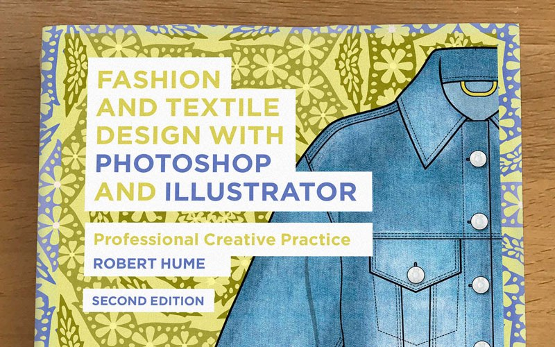 Close up photo of book 'Fashion and Textile Design with Photoshop and Illustrator' by BA Textile Design lecturer Robert Hume. The book is a greenish yellow colour with a repeat pattern and illustration of a blue denim jacket