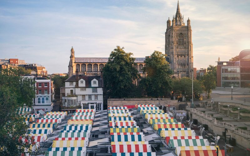 Norwich Market stalls with coloured tops with a picture of St Peter Mancroft in the background