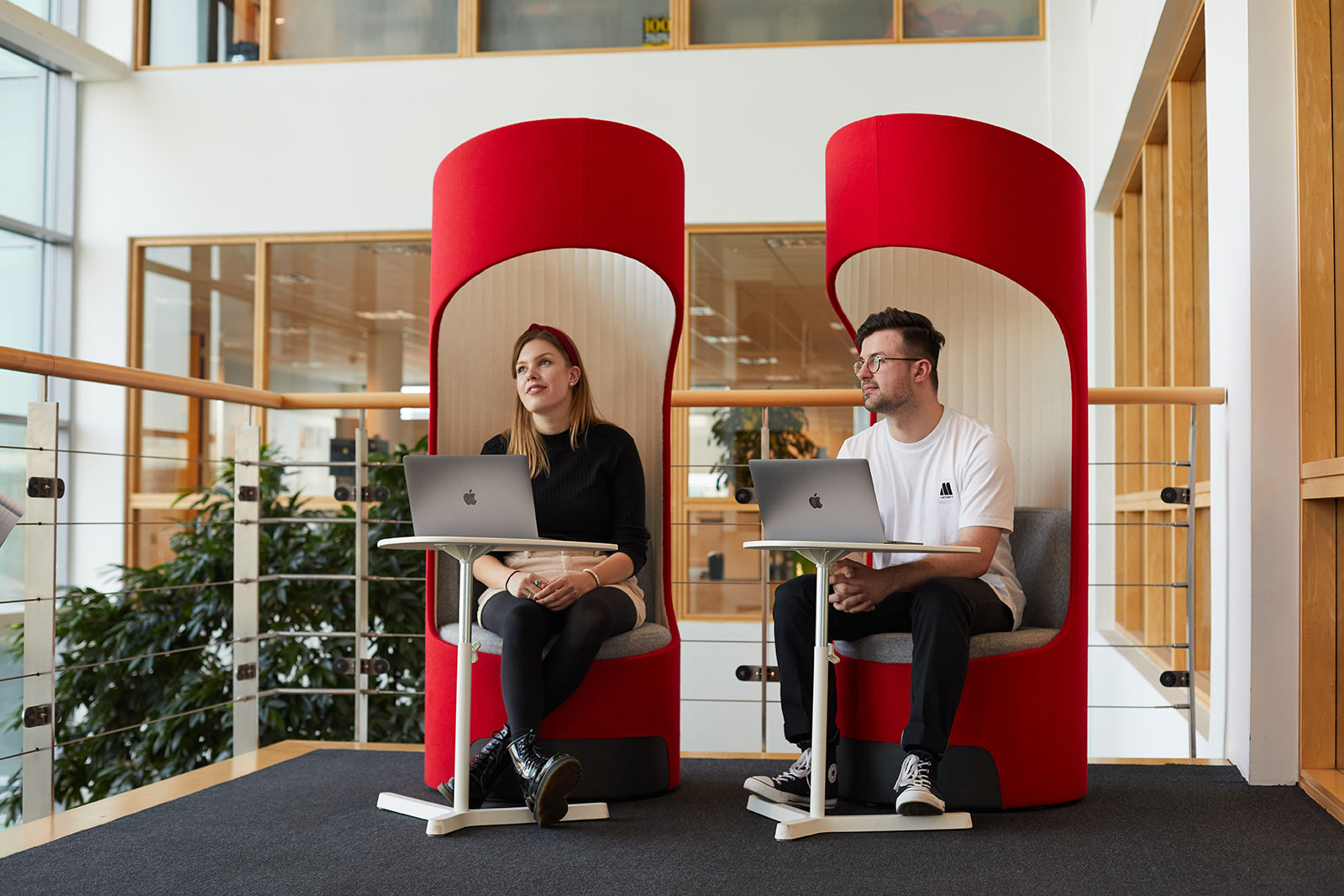 Elena Lockyer and Callum Brown sit in red pods in Redgate with their laptops in front of them