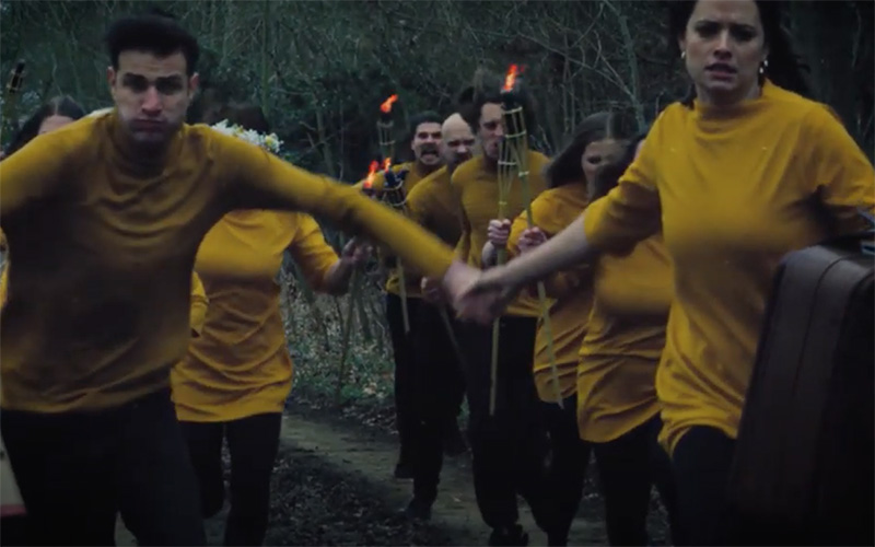 A group of people holding hands and wearing identical mustard coloured tops running in pairs towards the camera