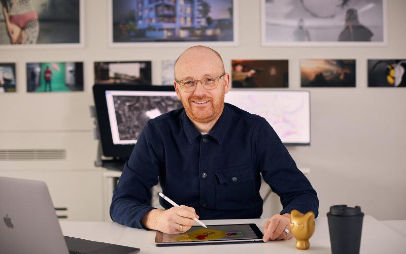 BA Animation Lecturer Jon Dunleavy sat in Norwich University of the Arts animation base room with an ipad and laptop
