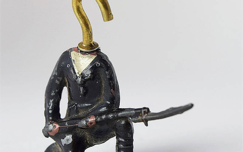 Small metal sculpture of a figure kneeling and holding a bayonette with a gold hook for a head