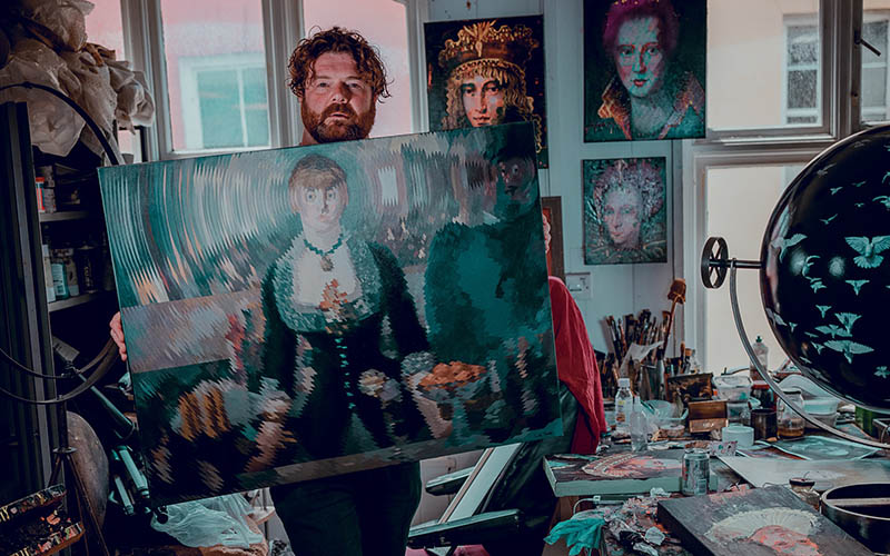 A man standing in a room surrounded by paintings, holding up a painting of a woman and looking at the camera