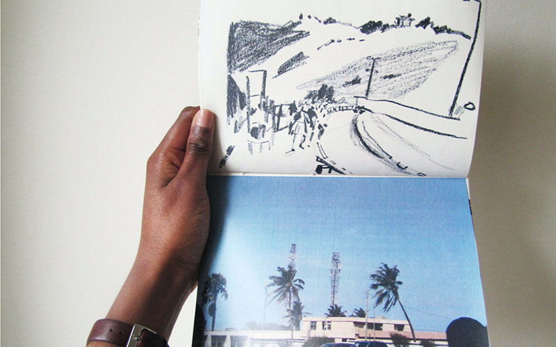 A hand holding up a sketchbook with a photo on the lower page and a drawing of the photo above