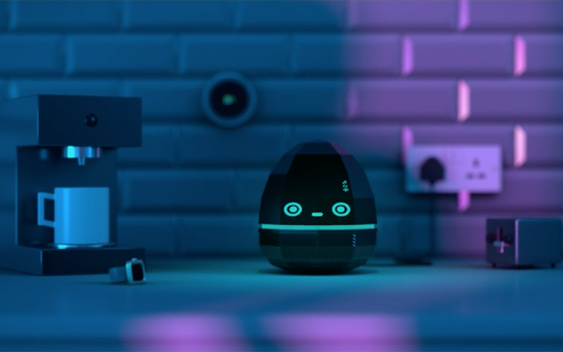 Animation still in mainly purple showing a small round robot with bright blue eyes sitting on a kitchen counter