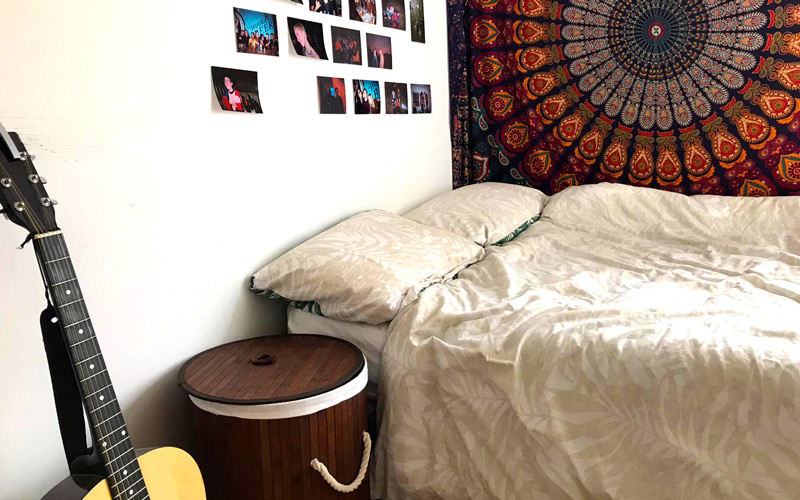 My Student Home: Inside BA Illustration student Patricia Mercer-David's double bedroom. There is a large patterned tapestry on the wall, alongside photographs. There is a double bed and guitar just out of shot