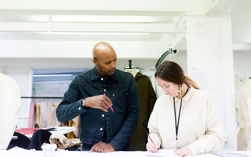 Fashion technician and a student at Norwich University of the Arts in the fashion studio looking at a collection