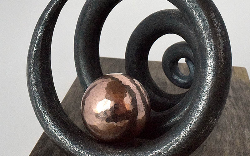 A metal sculpture made of a black spiral shape on a wooden surface, with a copper sphere resting inside