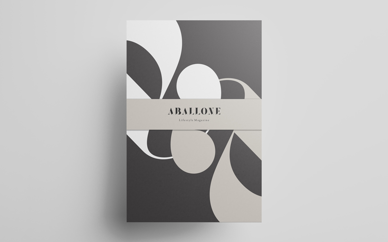 A mockup of Aballone postcards designed by BA Design for Publishing students Toby McLaren and Hannah Roadknight. The postcard is laid flat on a grey background. The design is comprised of two lower case a's, one white and one grey intertwined on an off-black background. There is a grey band around the middle holding the pack together, with the Aballone logo printed on top.