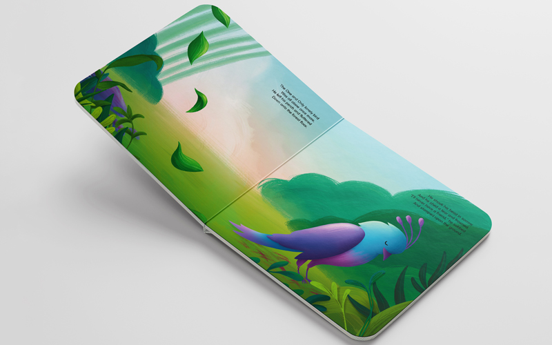 BA Illustration graduate Sophie Kent's highly commended entry into the Carmelite Prize. A mockup of a cardboard-style children's book, is open on an illustrated spread. The digital illustration shows a lonely bird of paradise with blue and purple feathers on the right hand page He standing on green grass, surrounded by foliage. The bird's head is bowed in sadness.