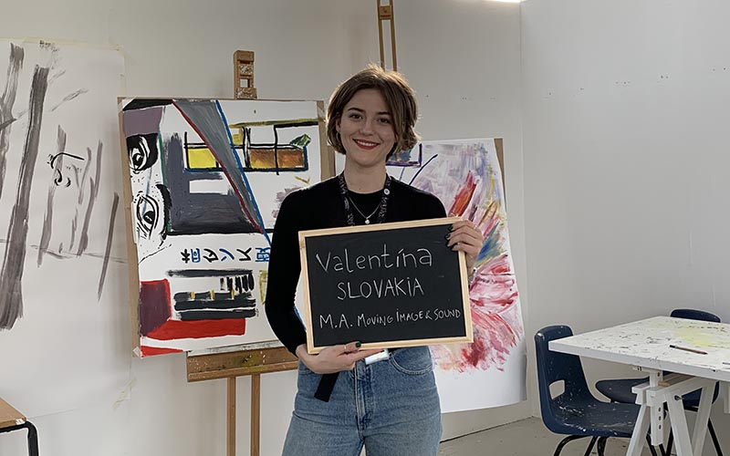 Photo of a young woman with short brown hair smiling at the camera and holding a blackboard saying Valentina Huckova MA Moving Image and Sound