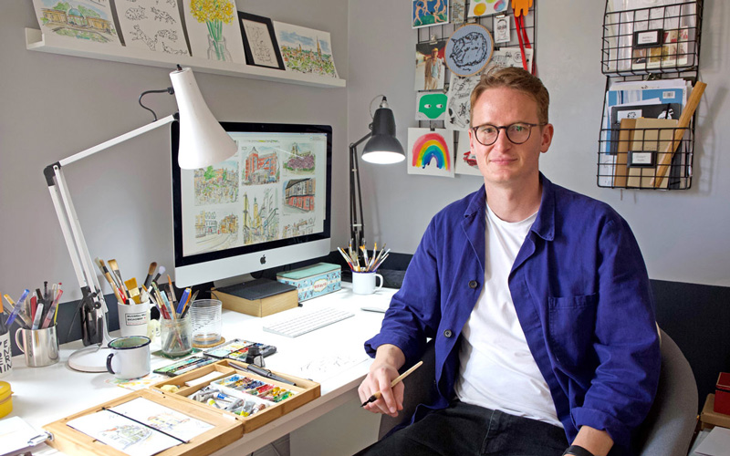 BA Graphic Design graduate Owen Mathers in his Norwich studio. Owen, who is wearing a blue shirt open over a white t-shirt, is sat at his desk, surrounded by his watercolour illustrations of Norwich