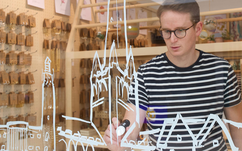 Owen Mathers at Lisa Angel in Norwich. Owen is standing inside the shop front, illustrating the Norwich cityscape directly onto Lisa Angel's front window, using thick white pen
