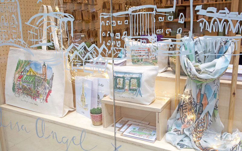 A photo of Lisa Angel's Norwich store front window display. Owen's white pen illustration of the city is on the inside of the window panes. On wooden shelving displays are the products Owen illustrated, including wash bags, scarves, tote bags and notebooks