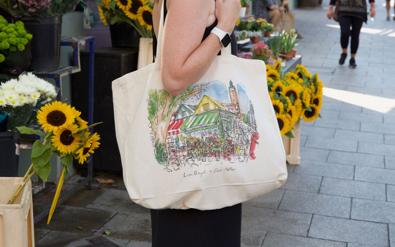 A woman standing in front of sunflowers at Norwich Market, wearing the tote bag illustrated by Owen Mathers for Lisa Angel. The illustration is watercolour and pen, and is of the flower stall in the market, with City Hall in the background