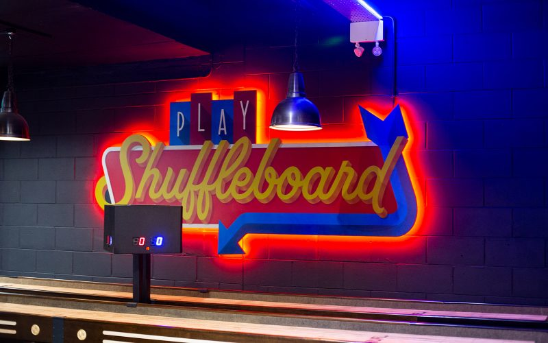 Bright neon lights saying Shuffleboard in the Boom Battle Bar, Norwich